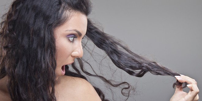 Young girl looking in damaged hair with strong expression